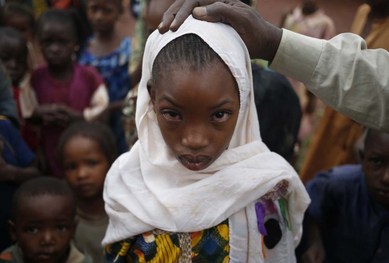 A sick girl from Puel tribe stands in a village outside Bambari May 30. Puel cattle herder tribes are Muslims and are often attacked by Anti-Balaka Christian militia.   || PHOTO CREDIT: GORAN TOMASEVIC  - REUTERS