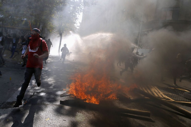 Student protesters run away during a demonstration to demand changes in the Chilean education system, in Santiago May 8, 2014. Thousands of students marched through the Chilean capital on Thursday for the first time since President Michelle Bachelet took power, ratcheting up the pressure on her to fulfill her campaign pledges to overhaul education in the country. (REUTERS/Ivan Alvarado)