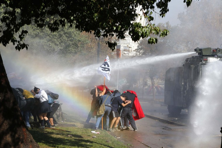 Student demonstrators take cover from a jet of water released from a riot police vehicle during a demonstration to demand changes in the Chilean education system, in Santiago May 8, 2014. Thousands of students marched through the Chilean capital on Thursday for the first time since President Michelle Bachelet took power, ratcheting up the pressure on her to fulfill her campaign pledges to overhaul education in the country. (REUTERS/Ivan Alvarado)