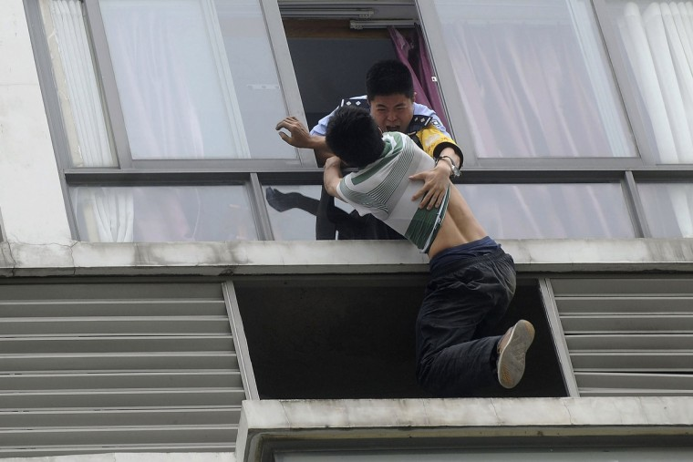 A police officer (top) grabs a man who tries to jump off the seventh floor of a hotel, in Chengdu, Sichuan province. The 32-year-old man attempted to commit suicide on Monday after a failed relationship. Police and his ex-girlfriend managed to talk him down 3 hours later, local media reported. (Reuters)