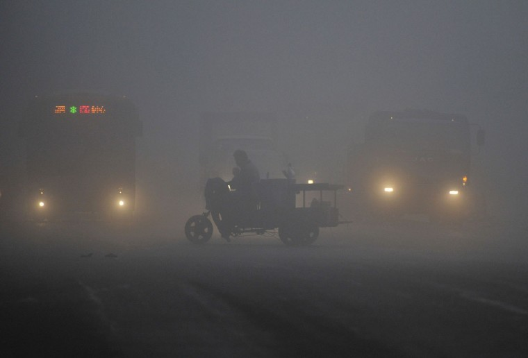 A tricycle travels past a crossroad on a hazy day in Hefei, Anhui province March 30, 2014. China plans to take more than 5 million ageing vehicles off its roads this year in a bid to improve air quality, with 330,000 cars set to be decommissioned in Beijing alone, the government said in a policy document published on Monday. (REUTERS/Stringer)