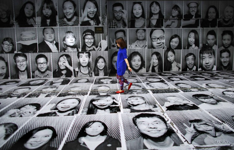A woman walks through a display of portraits which were made as part of the Inside Out art project by French artist JR at Xintiandi area in downtown Shanghai. JR and his team set up a photo studio and printing equipment in a truck to capture portraits of locals and tourists, which are then displayed in public. The portraits will be pasted on walls in the Lakeside Road area in Xintiandi. (Carlos Barria/Reuters)