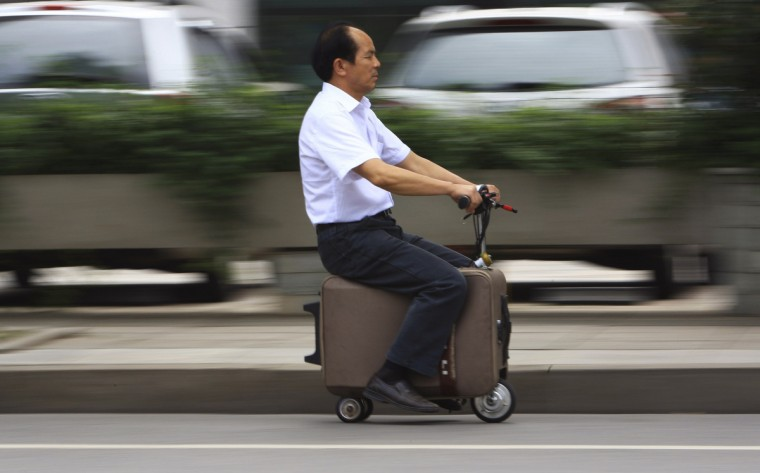 He Liang rides his home-made suitcase vehicle along a street in Changsha, Hunan province. He spent 10 years modifying the suitcase into a motor-driven vehicle. The suitcase has a top speed of up to 20km/h and the power capacity to travel up to 50-60km after one charge, according to local media. (China Daily)