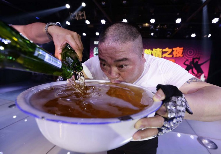 A singer drinks from a huge bowl of beer on-stage as he pays tribute to the customers after performing at an entertainment club in Beijing May 8, 2014. Picture taken May 8.  || PHOTO CREDIT: JASON LEE  - REUTERS