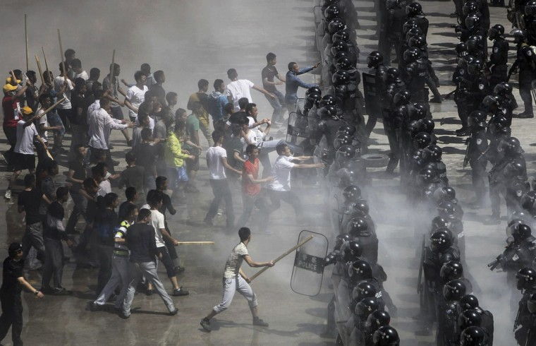 Mock rioters (L) clash with riot policemen during an anti-terrorist drill in Beijing, May 29, 2014. Over 2,800 people from Beijing police forces attend this drill on Thursday as China starts to launch a year-long nationwide anti-terrorism operation after fatal attacks in Xinjiang and other parts of the country. According to security authorities, a major part of that campaign is combat drills to test police officers' readiness and responses, Xinhua News Agency reported. REUTERS/China Daily