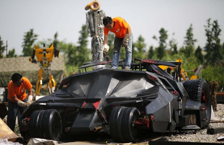 "Men paint a ""Batmobile"" replica on the outskirts of Shanghai, May 30. Li Weilei, the owner of the replica and a local businessman, uses his spare time and money to build replicas like the ""Batmobile"", Formula One cars and ""Transformers"" for rent or sale. Li spent around 75,000 yuan ($12,000) to build the model.   