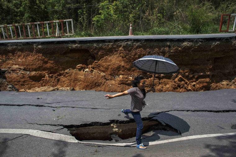 A woman with an umbrella jumps over a hole on a highway road, damaged by Monday's earthquake in Chiang Rai, in northern Thailand. The earthquake of 6 magnitude struck northern Thailand on Monday causing some damage to buildings and roads and knocking goods off shelves in shops but there were no immediate reports of any casualties. The quake struck 17 miles (27 km) southwest of the town of Chiang Rai, the U.S. Geological Survey (USGS). It was felt in the Thai capital, Bangkok, and in neighbouring Myanmar. (Athit Perawongmetha/Reuters)