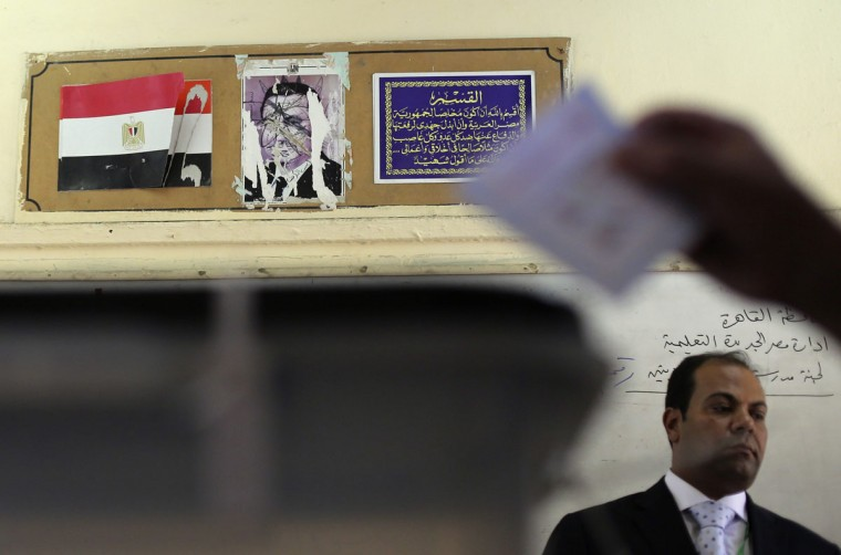 A torn picture of ousted former President Hosni Mubarak (top) is seen as a man casts his ballot during a presidential election inside a polling station in Cairo May 26, 2014. Egyptians voted on Monday in a presidential election expected to sweep former army chief Abdel Fatah al-Sisi into office, with supporters brushing aside concerns about human rights and hailing him as the strong leader the country needs. (REUTERS/Amr Abdallah Dalsh)