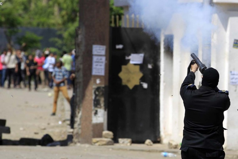 A member of the current Egyptian police force fires tear gas during clashes with student supporters of the Muslim Brotherhood and coup-deposed President Mohamed Mursi at the Al-Azhar University campus in Cairo's Nasr City district, May 9. The protesters marched towards Rabaa square, closing the roads, during a demonstration by members of the Muslim Brotherhood and the pro-Mursi Anti-Coup National Alliance against the military, interior ministry and presidential candidate Abdel Fattah al-Sisi, the former army chief whose coup deposed the Brotherhood's Mursi.   || PHOTO CREDIT: AMR ABDALLAH DALSH   - REUTERS