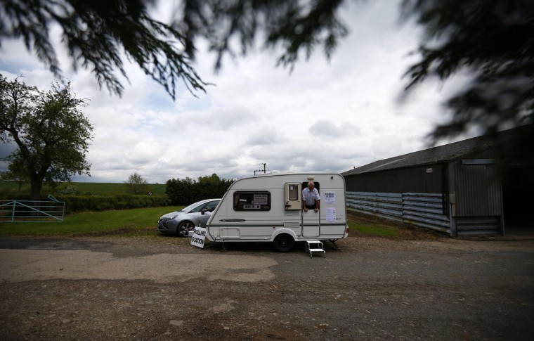 The presiding officer looks from a caravan being used as a polling station on Grange Farm during local council and European elections, Garthorpe in central England May 22, 2014. REUTERS/Darren Staples
