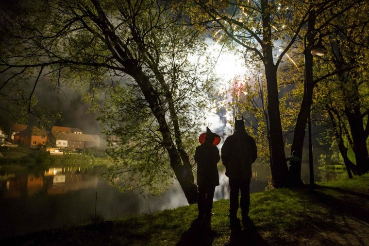 People stand by a lake as they watch fireworks explode over a Walpurgisnacht pagan festival in the town of Stiege, in the Harz mountain region, April 30, 2014. Legend has it that on Walpurgisnacht or May Eve, witches fly their broomsticks to meet the devil at the summit of the Brocken Mountain in Harz. In towns and villages scattered throughout the mountain region, locals make bonfires, dress in devil or witches costumes and dance into the new month of May. Picture taken April 30, 2014. (REUTERS/Thomas Peter)