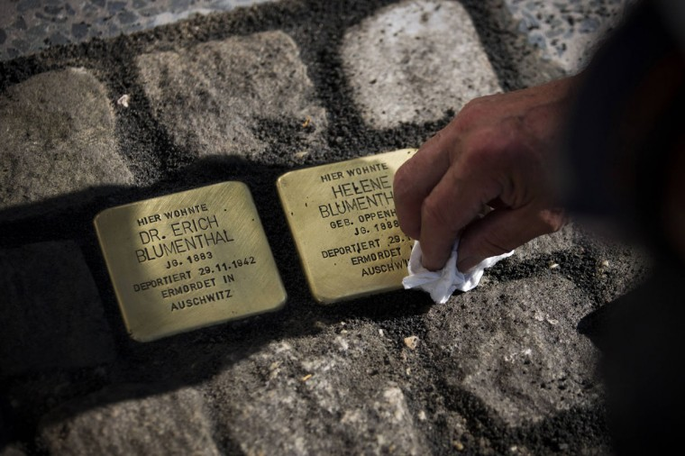 """German artist Gunter Demnig cleans two newly laid pieces of the Holocaust memorial project """"Stolpersteine"""" (stumbling blocks) after placing them into the pavement outside a residential building in Berlin, April 25, 2014. The blocks read: """"Here lived Dr. Erich Blumenthal, born 1883, deported 29.11.1942, murdered in Auschwitz. Here lived Helene Blumenthal, born 1888, deported 29.11.1942, murdered in Auschwitz."""" In Berlin, the blocks, which commemorate victims of the Holocaust, have become part of the fabric of the city, their plates glinting amid the grey paving on residential streets and stopping both locals and tourists in their tracks. Demnig, in 1996 illegally laid the first 41 in the Berlin neighbourhood of Kreuzberg, having found the names in a local history book about the area's Jewish population. Three months later, the city granted Demnig permission to legally proceed with the project. Today there are 45,000 """"Stolpersteine"""" in Germany and 16 other European countries. Berlin alone has 5,500 of them. Picture taken April 25. (REUTERS/Thomas Peter)"""