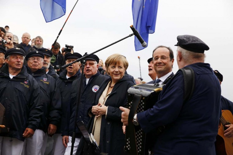 German Chancellor Angela Merkel and French President Francois Hollande listen to a Shanty choir before embarking on the ship Nordwind in Sassnitz on Ruegen island May 9.         || PHOTO CREDIT: THOMAS PETER  - REUTERS