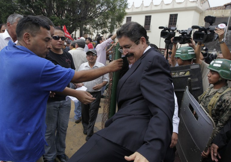 Former Honduras' president Manuel Zelaya (C) steps over a barricade outside congress in Tegucigalpa May 14, 2014. Zelaya was evicted from congress on Tuesday, alongside his wife, former presidential candidate Xiomara Castro, and nearly 40 other congress members who were staging a sit in over claims they had been blocked from debating critical national policies regarding the economy and security.Tensions between the left and right in Honduras have been high since ruling National Party's Juan Hernandez, who is head of Congress, won last year's election with 36.8 per cent of the votes, according to the country's election tribunal. But the leftist opposition had rejected the vote, saying the result was tainted by fraud. (REUTERS/Jorge Cabrera)