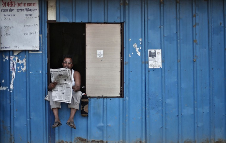 A man reads a newspaper as he sits on the window of a temporary shelter for homeless people in New Delhi. (Adnan Abidi/Reuters)
