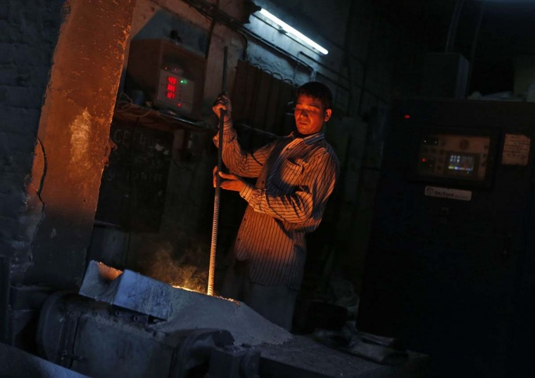A worker melts iron to make automobile parts inside a factory on the outskirts of the western Indian city of Ahmedabad May 12, 2014. India's ailing economy showed little sign of improvement on Monday, trapped in a spell of weak growth and high inflation when the country is on the cusp of political change that is widely expected to script an economic revival. (Amit Dave/Reuters)