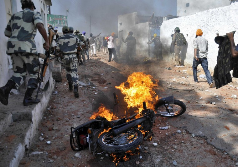 A motorcycle set on fire by a mob burns during clashes between two communities on the outskirts of the southern Indian city of Hyderabad. Two people were killed when police opened fire to control mobs following communal clashes on Wednesday on the outskirts of the city, local media reported. (Reuters)