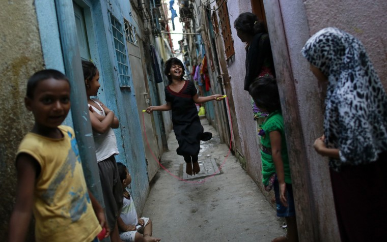 A girl jumps rope in an alley as others watch in Dharavi, one of Asia's largest slums, in Mumba. (Danish Siddiqui/Reuters)