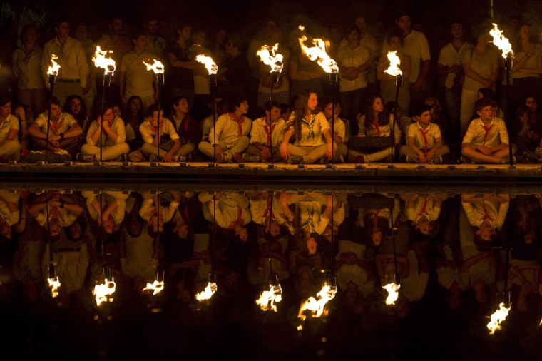 Israeli scouts are reflected in the pool of a monument as they sit next to torches during a ceremony marking Memorial Day at the Mount Herzl military cemetery in Jerusalem May 4, 2014. Israel commemorates its fallen soldiers on Memorial Day, which begins on Sunday night. (Nir Elias/Reuters)