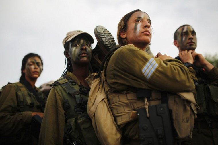 """Israeli soldiers of the Caracal battalion carry their comrade on a stretcher during a 20-kilometre march in Israel's Negev desert, near Kibbutz Sde Boker, marking the end of their training, May 29, 2014. The """"Caracal"""" battalion, two-thirds of whose members are women, was established in 2004 with the purpose of incorporating female soldiers in combat units. The main mission of Caracal is routine patrols on Israel's border with Egypt to intercept infiltrators and smuggling from the Sinai desert. REUTERS/Amir Cohen"""