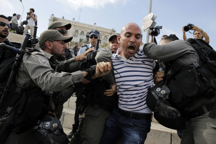 Israeli border policemen detain a member of media during clashes at protest against a parade by Israelis marking Jerusalem Day, at Damascus Gate in Jerusalem's Old City May 28, 2014. Nine Palestinians were detained on suspicion of throwing stones at policemen and participants of the parade, an Israeli police spokesman said on Wednesday. Jerusalem Day marks the anniversary of Israel's capture of the Eastern part of the city during the 1967 Middle East War. In 1980, Israel's parliament passed a law declaring united Jerusalem as the national capital, a move never recognised internationally. REUTERS/Ammar Awad