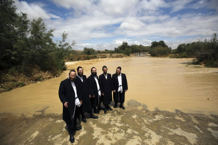 Ultra-Orthodox Jewish men pose for a friend to take their photograph near the flooded Besor stream in Israel's southern Negev desert near Kibbutz Zeelim May 8, 2014. Unseasonal heavy rain showers hit Israel on Thursday. (REUTERS/Amir Cohen)