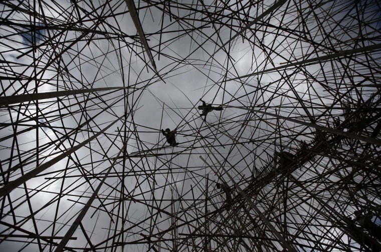 """Professional rock climbers work on the art installation """"Big Bambu: 5,000 Arms to Hold You"""" at the Israel Museum in Jerusalem May 12, 2014. The installation by artists Doug and Mike Starn, which upon completion will be made of 10,000 bamboo stalks and cover an area of more than 700 sq. meters,will open to the public June 10, 2014, a museum spokesperson said on Monday. (Ronen Zvulun/Reuters)"""