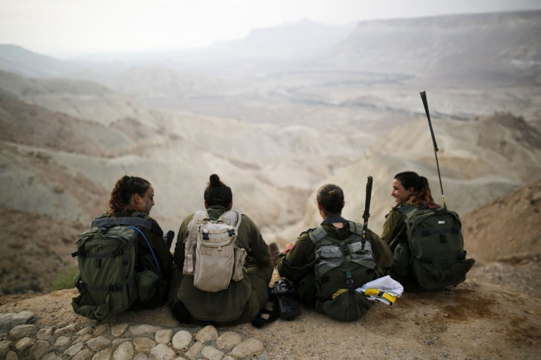"""Israeli soldiers of the Caracal battalion rest after finishing a 20-kilometre march in Israel's Negev desert, near Kibbutz Sde Boker, marking the end of their training, May 29, 2014. The """"Caracal"""" battalion, two-thirds of whose members are women, was established in 2004 with the purpose of incorporating female soldiers in combat units. The main mission of Caracal is routine patrols on Israel's border with Egypt to intercept infiltrators and smuggling from the Sinai desert. REUTERS/Amir Cohen"""