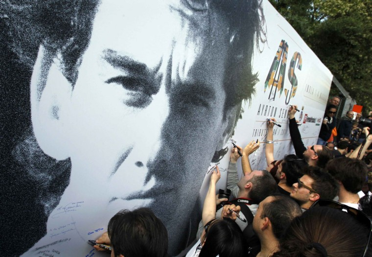 People sign a board with an image of Brazilian Formula One driver Ayrton Senna during a memorial at the Imola race track, northern Italy May 1, 2014. A tribute event was held at Imola race track in memory of Formula 1 drivers Senna and Roland Ratzenberger to mark the 20th anniversary of their deaths. (REUTERS/Alessandro Garofalo)