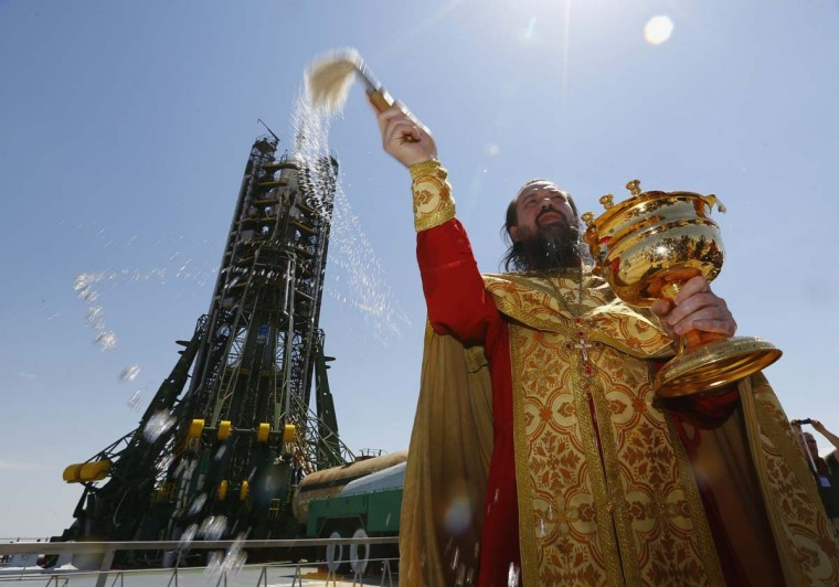 An Orthodox priest conducts a blessing in front of the Soyuz TMA-13M spacecraft set on the launch pad at Baikonur cosmodrome May 27, 2014. The Soyuz is scheduled to travel with Alexander Gerst of Germany, Gregory Wiseman of the U.S. and Maxim Surayev of Russia to the International Space Station on May 29. (Shamil Zhumatov/Reuters)