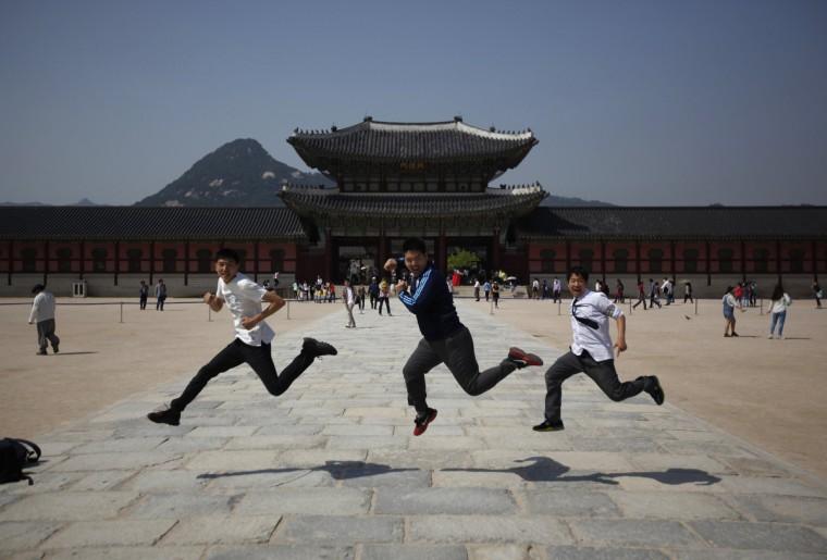 Students jump as they pose for photographs at Gyeongbok Palace in central Seoul. (Kim Hong-Ji/Reuters)