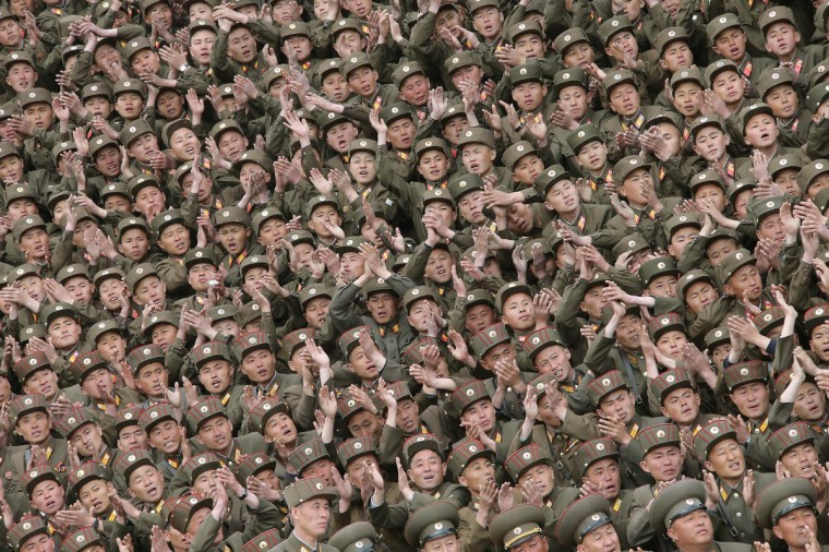 Soldier-builders of KPA Units 966, 462, 101, 489, who took part in building the workers' hostel of Kim Jong Suk Pyongyang Textile Mill, applaud during a photo session with North Korean leader Kim Jong Un in this undated photo released by North Korea's Korean Central News Agency (KCNA) in Pyongyang. (KCNA/Reuters)