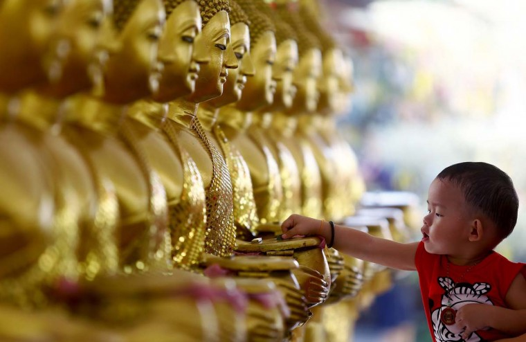 A child drops coins into golden Buddha statues as a symbol of blessings on Vesak Day at the Thai Buddhist Chetawan Temple in Petaling Jaya, near Kuala Lumpur May 13, 2014. Buddhists across the world on Tuesday celebrate holy Vesak to honour the birth, enlightenment and passing of Lord Buddha 2,550 years ago. (Samsul Said/Reuters)