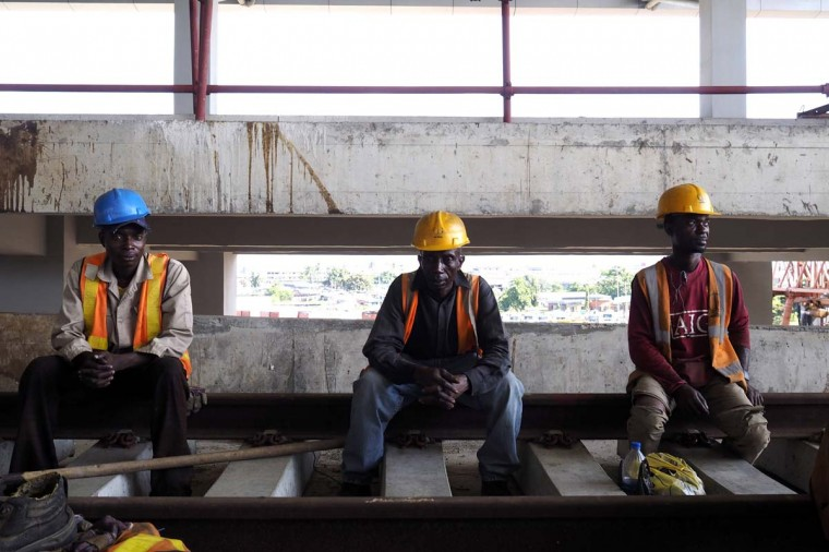 Men take a break from work at the National Arts Theatre stop of the light rail system under construction in Lagos, Nigeria, May 30. Started in 2009 to ease traffic, Lagos state government is building a rail system with the China Civil Engineering Construction Corporation. The first test runs should start in 2015, according to an official at the National Arts Theatre work site.  || PHOTO CREDIT: JOE PENNEY  - REUTERS