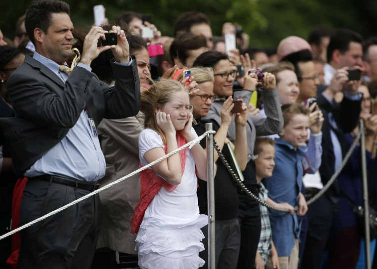 A crowd of spectators is buffeted by the rotor wash of the Marine One helicopter as President Barack Obama lands on the South Lawn at the White House in Washington, May 15, 2014. The president is returning from a trip to New York to attend the opening of the National September 11 Memorial Museum. (REUTERS/Jim Bourg)