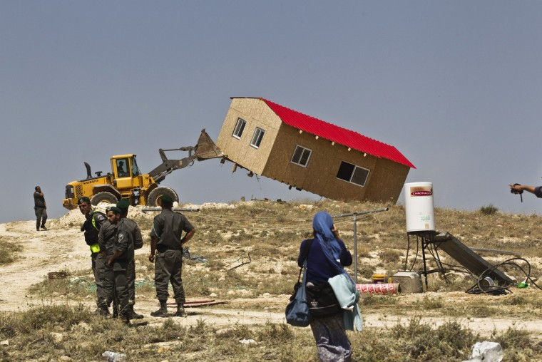Israeli border policemen stand near a bulldozer as it demolishes a temporary structure in the West Bank Jewish settler outpost of Maale Rehavam, near to Bethlehem. Some seven structures were razed on Wednesday by Israeli border police officers and no injuries or arrests were made during the incidences, a police spokesman said on Wednesday. The structures were demolished as part of Israel's continuing effort to remove settlements built without government authorization. (Ronen Zvulun/Reuters)