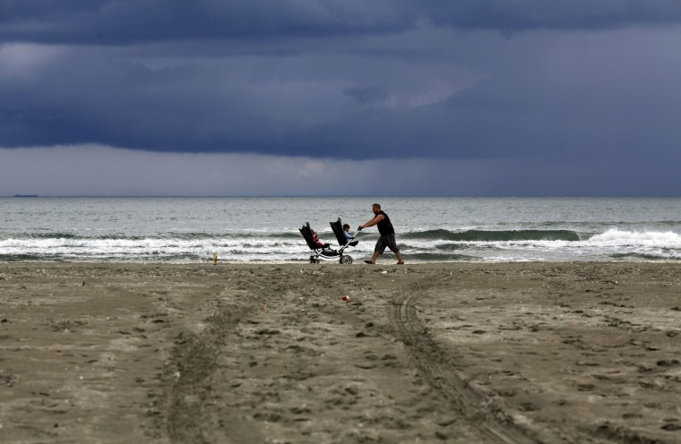 A man pushes a pram with two children by the Black Sea beach after a heavy rain in Navodari, Romania. (Radu Sigheti/Reuters)
