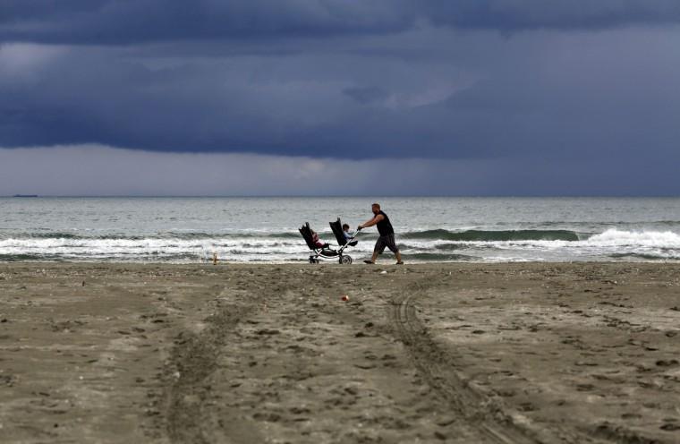 A man pushes a pram with two children by the Black Sea beach after a heavy rain in Navodari, Romania. (Radu Sigheti/Reuters)