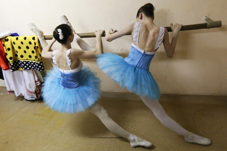 Students of the Krasnoyarsk choreographic college stretch backstage before a dress rehearsal of a performance by graduates of the college at the State Theatre of Opera and Ballet in Russia's Siberian city of Krasnoyarsk. The annual performance showcases the work of students from across Russia who study or have studied at the well-known school. (Ilya Naymushin/Reuters)