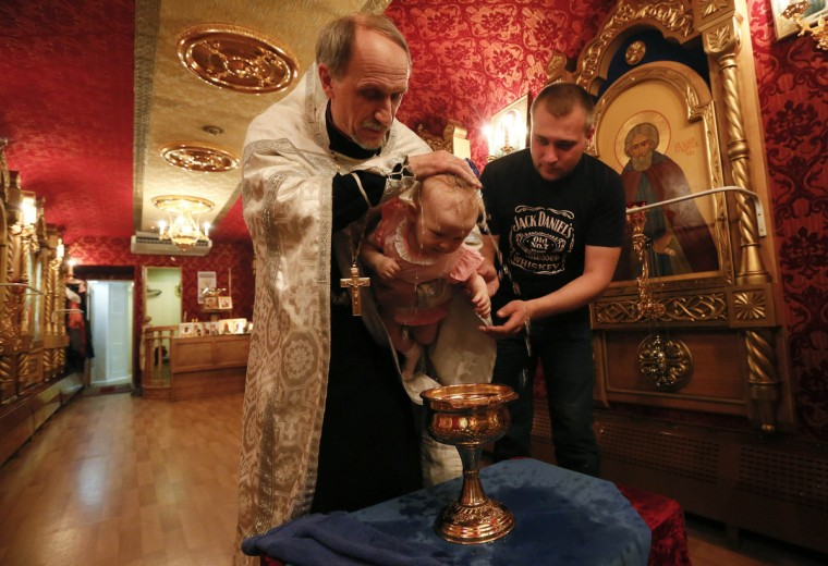 An Orthodox priest baptizes a baby at a church inside the Doctor Voino-Yasenetsky Saint Luka train, which serves as a free consultative and diagnostic medical centre, at a railway station of Divnogorsk, outside Russia's Siberian city of Krasnoyarsk. The train transports well-qualified medical personnel and equipment to assist about 200 patients a day and has been traveling annually from the main regional centre Krasnoyarsk to distant settlements of Krasnoyarsk and Khakassia Regions, where hospitals and clinics are scarce, for the last seven years. The train also has a carriage which operates as a mobile Orthodox church. The train was named after an outstanding Russian surgeon, an Orthodox bishop and GULAG prisoner Valentin Voino-Yasenetsky. (Ilya Naymushin/Reuters)