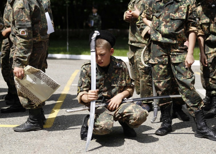 "A student from the General Yermolov Cadet school rests on his sword during the ""Last Bell"" ceremony to mark the end of the school year in Stavropol. The General Yermolov Cadet School in the southern Russian city of Stavropol is a state-run institution that teaches military and patriotic classes in addition to a normal syllabus. (Eduard Korniyenko/Reuters)"