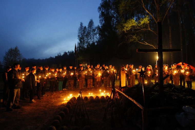 People attend a prayer service to commemorate Soviet war victims, while standing near their remains, as students from the General Yermolov Cadet School take part in an all-Russian search operation to find and rebury the remains of Red Army soldiers killed during World War Two in the village of Bolshoye Tishovo, southeast of Smolensk in western Russia May 3, 2014. Some 600 people from different Russian regions, including students of the General Yermolov Cadet School, took part in the multi-day search operation which ended on May 6. Participants managed to recover the remains of more than 200 Red Army soldiers, 25 of whom were identified, according to organizers. The General Yermolov Cadet School, based in the southern Russian city of Stavropol, is a state-run institution that teaches military and patriotic classes in addition to a normal syllabus. Russia celebrates victory over Nazi Germany on May 9. Picture taken May 3, 2014. (REUTERS/Eduard Korniyenko)