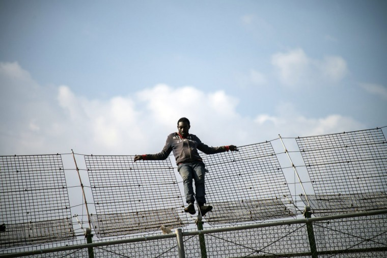 An African migrant rests on a border fence covered in razor wire during a latest attempt to cross into Spanish territory, between Morocco and Spain's north African enclave of Melilla May 1, 2014. Around 400 people stormed the border and at least 150 of them reached European territory, according local authorities. (REUTERS/Jesus Blasco de Avellaneda)