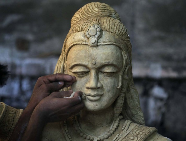 A man cleans a statue of Buddha which will be featured in an illuminated display illustrating episodes from the life of Buddha, ahead of Vesak Day celebrations in Colombo on May 9. Vesak Day, which is celebrated on May 14 and 15 in Sri Lanka, commemorates the birth, enlightenment and death of Buddha.  || PHOTO CREDIT: DINUKA LIYANAWATTE  - REUTERS