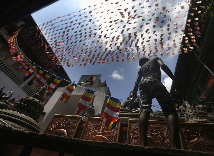 A man holds a line of Buddhist flags while decorating a pandal at a temple ahead of Vesak Day celebrations in Colombo May 13, 2014. Vesak Day, which is celebrated on May 14 and 15 in Sri Lanka, commemorates the birth, enlightenment and death of Buddha. (Dinuka Liyanawatte/Reuters)