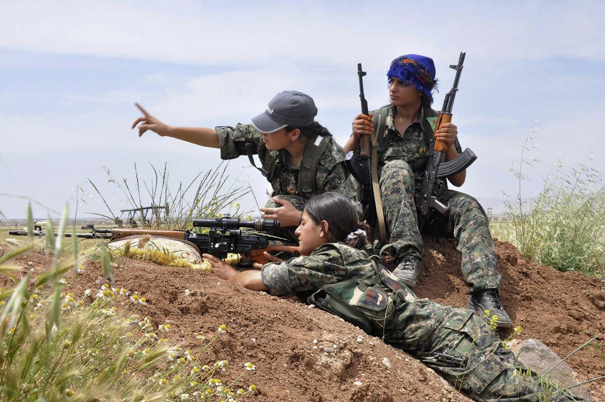 Kurdish female fighters of the Women Protection Unit (YPJ) attend