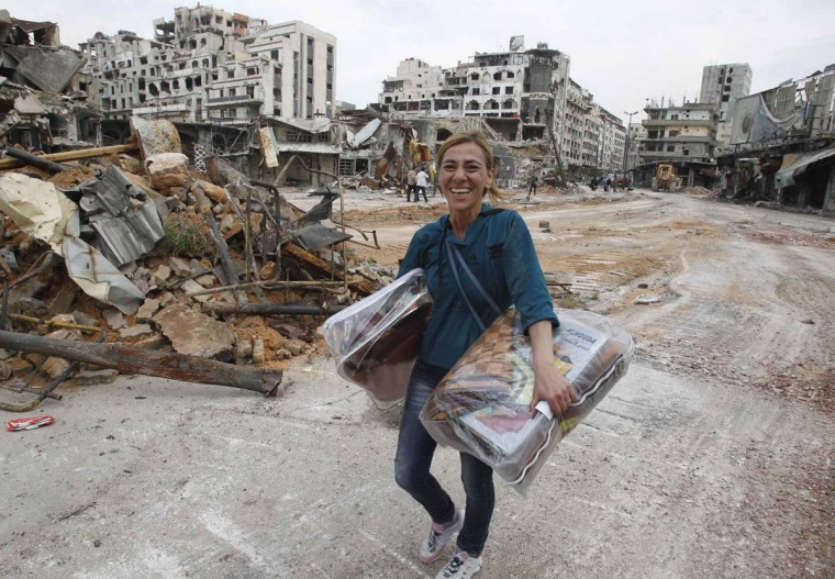 A woman reacts to the camera as she carries some items from her home following the cessation of fighting between rebels and forces loyal to Syria's President Bashar al-Assad at al-Hamdeya neighborhood in Homs city May 9. Around 270 Syrian rebels granted safe exit under a complex deal with President Bashar al-Assad's forces are being held in Homs by the army after insurgents elsewhere failed to uphold their side of the agreement, Syrian officials said on Friday. Following a year of siege, around 1,200 rebels and residents in the Old City of Homs left the city on buses this week in exchange for the release of dozens of captives held by rebels in the northern provinces of Aleppo and Latakia.  || PHOTO CREDIT: KHALED AL-HARIRI  - REUTERS