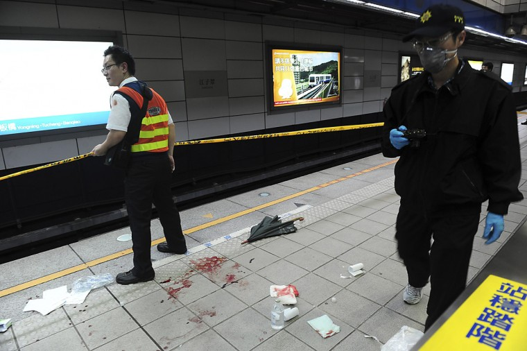 A crime scene investigator walks at the scene of a knife attack at a subway platform in the Taipei Metro Jiangzicui station in New Taipei city. A knife-wielding college student killed three people and injured 25, police said, in the rare incident on Taipei's metro on Wednesday. Police said a motive was not immediately clear, although the man had been drinking alcohol before the attacks. (Reuters)