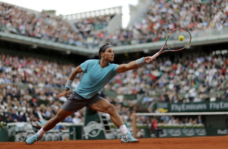 Rafael Nadal of Spain stretches out to hit a return to Dominic Thiem of Austria during their men's singles match at the French Open tennis tournament at the Roland Garros stadium in Paris May 29, 2014. REUTERS/Jean-Paul Pelissier