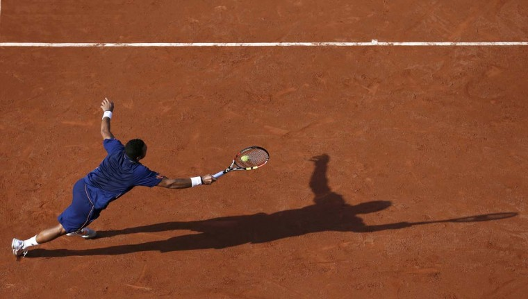 Jo-Wilfried Tsonga of France stretches out to return a forehand to Jerzy Janowicz of Poland during their men's singles match at the French Open tennis tournament at the Roland Garros stadium in Paris on May 30.         || PHOTO CREDIT: VINCENT KESSLER  - REUTERS